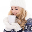 Beautiful girl in winter clothes with cup of tea isolated on whi — Stock Photo