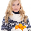 Beautiful girl in winter clothes with mandarins isolated on whit — Stock Photo