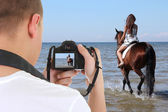 Man with camera taking picture of beautiful woman on the horse — Stock Photo