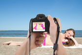 Dslr camera in male hands taking picture of beautiful woman on t — Stock Photo