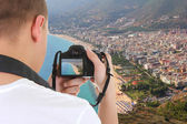 Camera in male hands taking picture of beautiful landscape in Al — Stock Photo