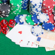 Stock Photo: Dice, four aces, colorful poker chips and money on a green felt