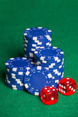 Blue poker chips and two cubes on the green table — Stock Photo