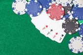 Poker chips and playing cards on a green table background — Stock Photo