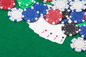 Poker chips and four aces on a green table background — Stock Photo