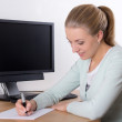 Stock Photo: Young secretary doing paperwork in office