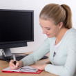 Foto de Stock  : Young blondie womwriting in notebook