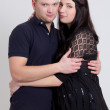 Young beautiful pregnant woman and her husband over grey — Stock Photo #38650557