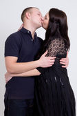 Young beautiful pregnant woman and her husband kissing over grey — Stock Photo