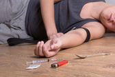 Syringe with drugs and addict lying on the floor — 图库照片