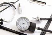 Close up of clipboard with blank paper sheet, stethoscope and sp — Stock Photo