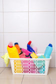 Cleaning supplies in plastic basket on tiled floor — Stock Photo