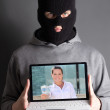 Masked man with computer with picture of woman giving money — Stock Photo
