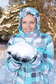 Woman in blue checkered jacket with snow in hands in winter fore — Stock Photo