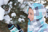 Woman in blue sporty checkered jacket with snow in hands in wint — Stock Photo