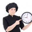 Portrait of young cook woman in black uniform with clock isolate — Stock Photo