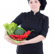 Young cook woman in black uniform with vegetables isolated on wh — Stock Photo