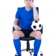 Bored man in uniform sitting with remote control and watching so — Stock Photo #41380093