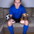 Supporter in uniform sitting on the sofa and watching football w — Stock Photo #41380145