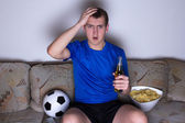 Shocked supporter in uniform sitting on the sofa and watching fo — Stock Photo