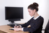 Beautiful successful business woman working in office and comput — Stock Photo
