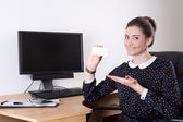 Beautiful business woman showing visiting card in office and pc — Stock Photo