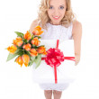 Funny beautiful woman holding gift box and flowers isolated on w — Stock Photo