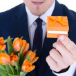 Man holding gift box with wedding ring and flowers isolated on w — Stockfoto