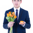 Young man in suit holding gift box with wedding ring and flowers — Stockfoto