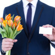 Business man in suit holding flowers and blank visiting card iso — Stock Photo #42023421