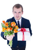 Funny young man with bunch of flowers and gift box isolated on w — Stock Photo