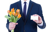 Business man in suit holding flowers and blank visiting card iso — Stock Photo