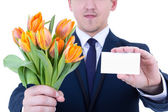 Flowers delivery - tulips and blank visiting card in male hands  — Stock Photo