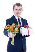 Romantic man giving gift box and flowers isolated on white — Stock Photo