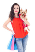 Attractive woman holding little dog yorkshire terrier and shoppi — Stock Photo