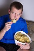 Ung man titta på tv hemma och äta chips — Stockfoto