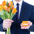 Proposal - man holding gift box with wedding ring and flowers is — Stock Photo