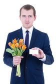Flowers delivery - young man in suit holding tulips and blank vi — Stock Photo