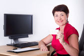 Middle aged businesswoman with visiting card sitting in office — Stock Photo