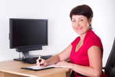 Middle aged businesswoman sitting in office — Stock Photo