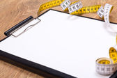 Close up of blank clipboard and measure tape on the table — Stock Photo