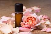 Bottle with essential oil and rose petals — Stock Photo