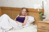 Cute woman sitting on her bed — Stock Photo