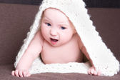 Funny baby girl in white woolen scarf crawling — Stock Photo