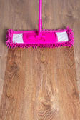Close up of wooden parquet floor with pink mop - before after — Stock Photo