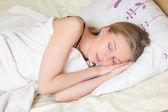 Cute young woman sleeping on bed — ストック写真