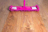 Close up of wooden floor with pink mop - before after — Stock Photo