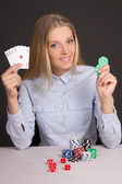 Beautiful blond woman with playing cards and poker chips over gr — Stock Photo
