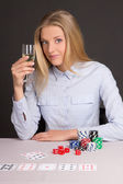 Young beautiful blond woman with glass of champagne playing poke — Stock Photo