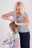 Woman brushing her daughter hair over white — ストック写真